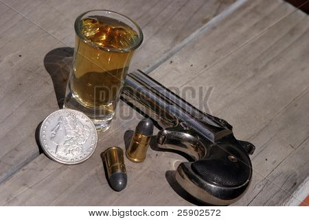 1889 darringer pistol with spare shells a  Morgan Silver Dollar, and a shot of wiskey on an old wood table