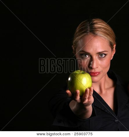 a healthy fit woman hands a fresh green apple to YOU the viewer healthy eating concepts eve passing adam an apple from the tree of knowledge concept