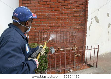 an unidentifiable person cleans graffiti off a wall in the Urban Jungle called  Los Angeles