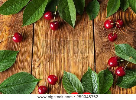Berries Of Cherries And Leaves Against Background Of Wooden Boards