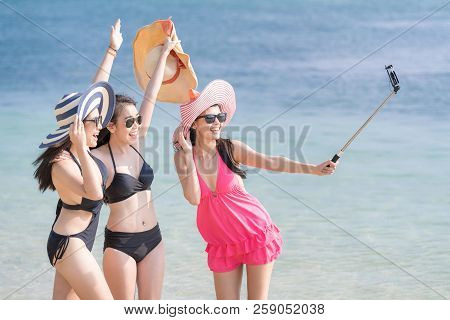 Group Of Friends Wearing Sun Glasses And Taking Selfie At The Beach On Summer Vacation. Happy Asian