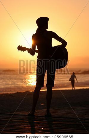 an unidentifiable young woman plays her guitar as the sun sets behind her in Laguna Beach California