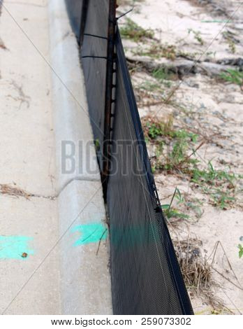 Sidewalk With Black Silt Contractor Fence Background