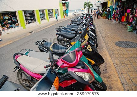Colorful Scooters Or Motorcycles For Sale Or Hire Standing In Row With Wheels And Lights On Street R