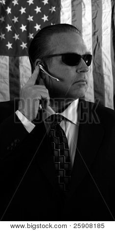a Secret Service Agent speaks on his ear piece in black and white