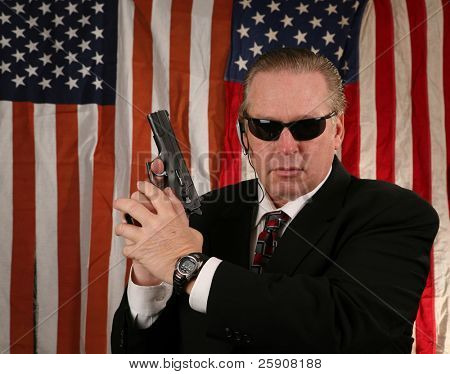 a Secret Service Agent holds his weapon at the ready position