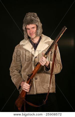 a man in a sheep skin jacket and a furry hat holds an antique