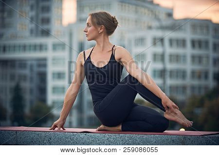 Beautiful Young Woman Practices Yoga Asana Ardha Matsyendrasana - Half Spinal Twist Pose Outdoors Ag