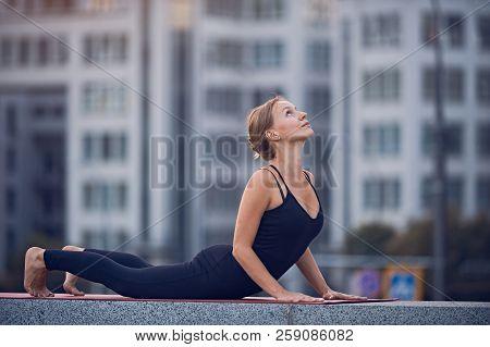 Beautiful Young Woman Practices Yoga Asana Upward Facing Dog Urdhva Mukha Svanasana Outdoors Against