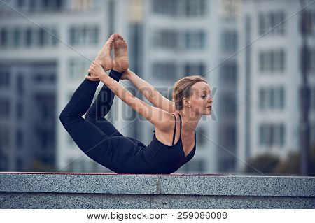 Beautiful Woman Practices Yoga Asana Dhanurasana - Bow Pose Outdoors Against The Background Of A Mod