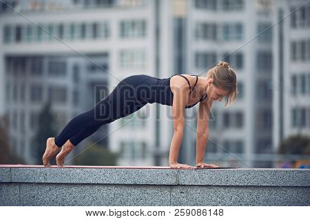 Beautiful Young Woman Practices Yoga Asana Chaturanga Dandasana - Four Limbed Staff Pose Outdoors Ag