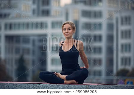Beautiful Young Woman Practices Yoga Asana Sukhasana - The Easy Sitting Crosslegged Pose Outdoors Ag