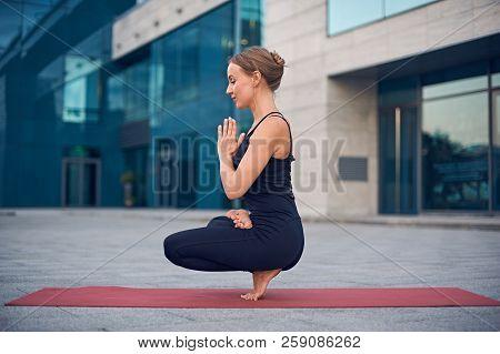 Beautiful Young Woman Practices Yoga Asana Padangustha Padma Utkatasana - Half Lotus Toe Balance Pos