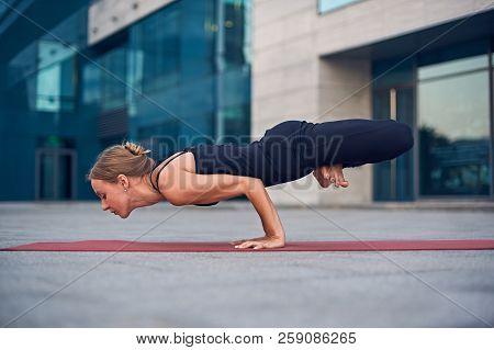Beautiful Young Woman Practices Yoga Asana Lotus Peacock Pose - Padma Mayurasana Outdoors Against Th