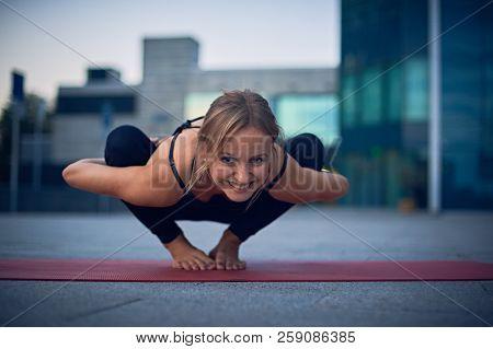 Beautiful Young Woman Practices Yoga Asana Malasana - Garland Pose Outdoors Against The Background O