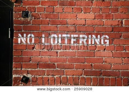 no loitering stencled onto a brick wall