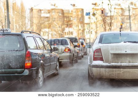 Cars Standing In Row In Traffic Jam On City Street On Slippery Snowy Road In Winter. Vehicles Get St