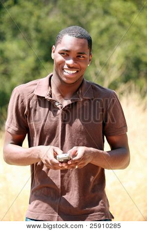 a handsome african american man smiles and responds while he text messages on his cell phone