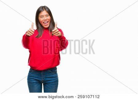 Young asian woman wearing winter sweater over isolated background approving doing positive gesture with hand, thumbs up smiling and happy for success. Looking at the camera, winner gesture.