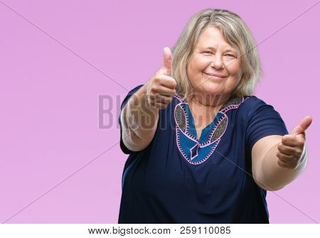 Senior plus size caucasian woman over isolated background approving doing positive gesture with hand, thumbs up smiling and happy for success. Looking at the camera, winner gesture.
