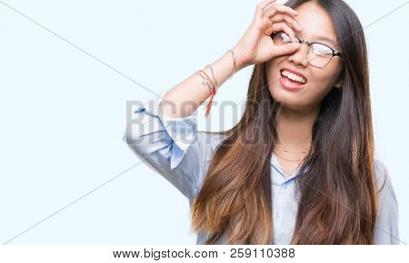 Young asian business woman wearing glasses over isolated background doing ok gesture with hand smiling, eye looking through fingers with happy face.