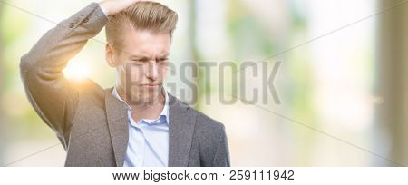 Young handsome blond business man confuse and wonder about question. Uncertain with doubt, thinking with hand on head. Pensive concept.