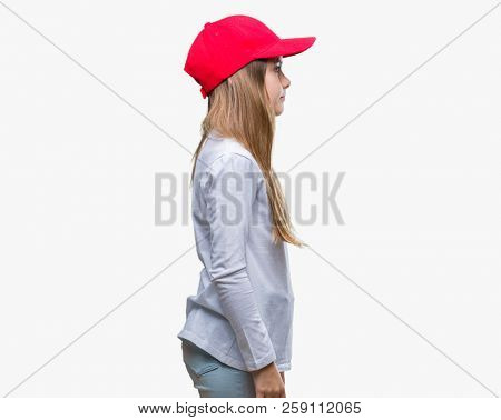 Young beautiful girl wearing red cap isolated background looking to side, relax profile pose with natural face with confident smile.