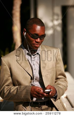 a well dressed man text messages on his cell phone outside while listening on his personal digital music player