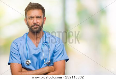 Adult hispanic doctor or surgeon man over isolated background skeptic and nervous, disapproving expression on face with crossed arms. Negative person. poster