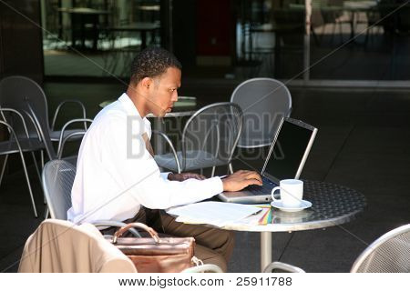 a business man works from his office at an outdoor coffee shop with his laptop and wireless internet connection
