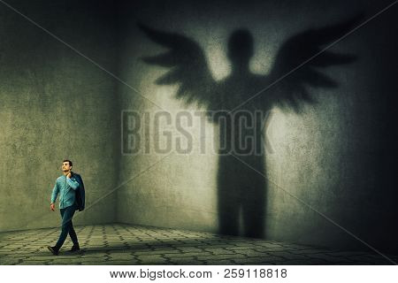Proud And Confident Young Businessman Casting A Superhero Shadow With Angel Wings On A Dark Room Wal