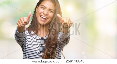 Young beautiful arab woman wearing sunglasses over isolated background approving doing positive gesture with hand, thumbs up smiling and happy for success. Looking at the camera, winner gesture.