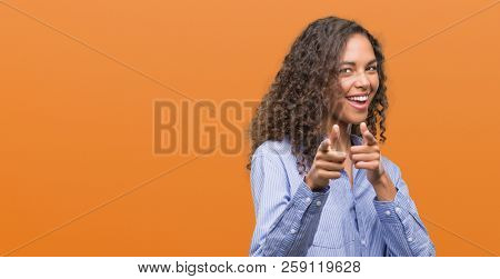 Young hispanic business woman pointing fingers to camera with happy and funny face. Good energy and vibes.