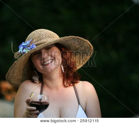 an attractive woman in a pretty and fun hat enjoys a glass of red wine by a pool one evening
