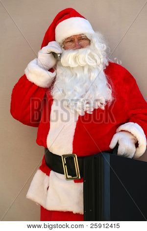 Santa Claus Holds a briefcase and talks on his cell phone