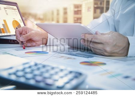 Businessman Is Deeply Reviewing A Financial Report For A Return On Investment Or Investment Risk Ana