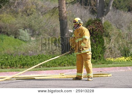 LAGUNA BEACH, CA - FEB 19: A firefighter in action during fire fighting drills at the local Fire Department training area on February 19, 2009 in Laguna Beach, California.
