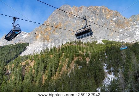 Alpine Scenery With The Rocky Peaks Of The Alps Mountains And Ski Lifts Rolling On A Cableway Over T
