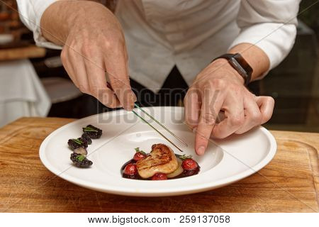 Chef is serving foie gras with berry sauce, haute cuisine French starter