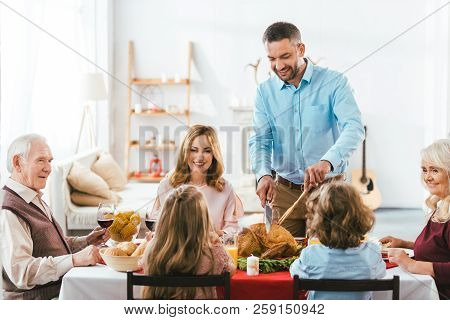 Big Family Having Delicious Thanksgiving Dinner Together At Home While Father Cutting Turkey