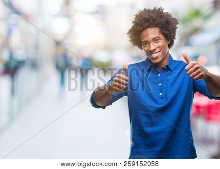 Afro american man over isolated background approving doing positive gesture with hand, thumbs up smiling and happy for success. Looking at the camera, winner gesture.
