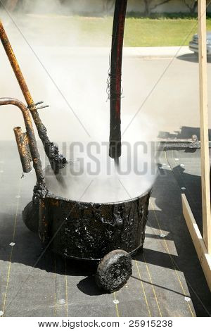 hot molten tar pours into a hot tar bucket on a roof