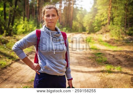 Young Woman In Green Autumn Forest. Portrait Of Cute Girl In Forest Nature. Hikes In Woodland. Hikin