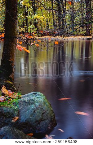 Mysterious Atmosphere At Tranquil Autumn Forest Lake. Calm Lake Surface, Long Exposure
