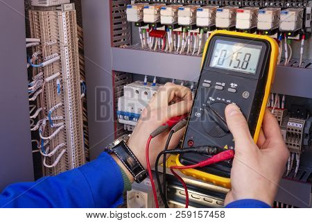 Multimeter In Hands Of Electrician Engineer In Electrical Cabinet. Maintenance Of Electric System. W