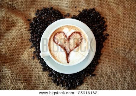 Coffee for Coffee Lovers, a cup of Coffee or  espresso with a Heart in the foam nestled in a bed of unground coffee beans on a burlap background