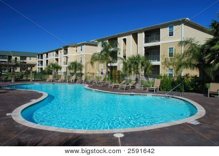 Residential apartment houses with a swimming pool poster
