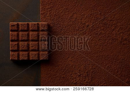 Top View Of Delicious Brown Cocoa Powder And Tasty Chocolate On Black Background