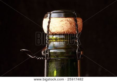 close up of a champagne bottle with its cork, on black velvet