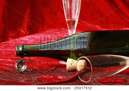 empty champagne glasses and bottle lay on wet red velvet after the party poster